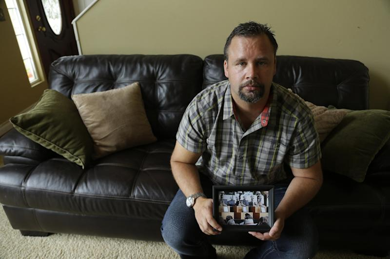 In this Saturday, Aug. 3, 2013, photo, retired U.S. Army Staff Sgt. Shawn Manning poses for a photo, at his home in Lacey, Wash. as he holds a photograph from the memorial for victims of a 2009 mass shooting at Fort Hood, Texas. Manning, who still carries two bullets in his body from the shooting that killed 13 people, is scheduled to testify at the court martial for Maj. Nidal Malik Hasan, the accused shooter this week. (AP Photo/Ted S. Warren)