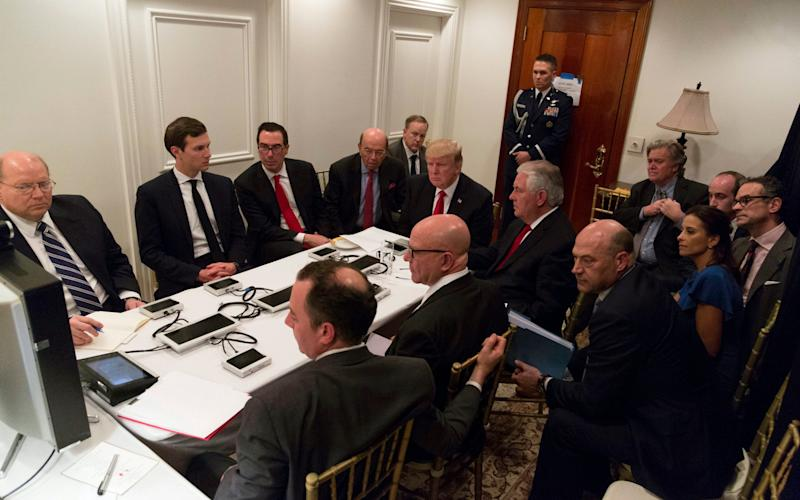 President Donald Trump receives a briefing on the Syria military strike from his National Security team, including a video teleconference with Secretary of Defense, Gen. James Mattis, and Chairman of the Joint Chiefs of Staff, Gen. Joseph Dunford, on Thursday, April 6, 2017, in a secured location at Mar-a-Lago in Palm Beach, Fla - Credit: AP
