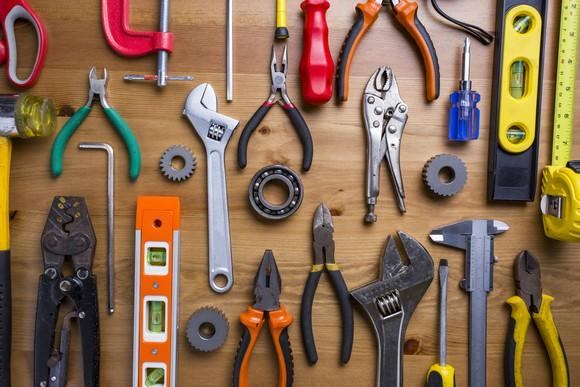 A wide variety of hand-held tools on a table.