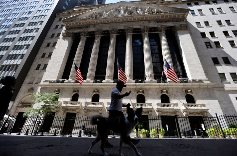 A man walks a dog in the shade past the New York Stock Exchange (NYSE) during hot weather in New York