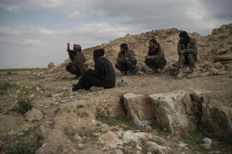 U.S.-backed Syrian Democratic Forces (SDF) fighters sit atop a hill in the desert outside the village of Baghouz, Syria, Thursday, Feb. 14, 2019. U.S.-backed Syrian forces are clearing two villages in eastern Syria of remaining Islamic State militants who are hiding among the local population, and detaining others attempting to flee with the civilians, the U.S.-led coalition said Thursday. (AP Photo/Felipe Dana)