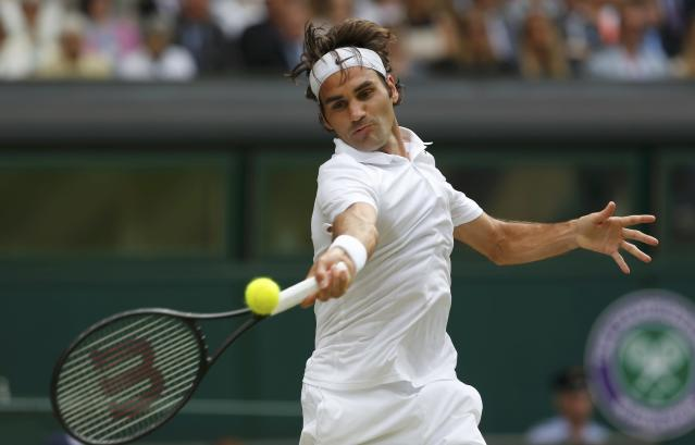 Roger Federer of Switzerland hits a return during his men's singles final tennis match against Novak Djokovic of Serbia at the Wimbledon Tennis Championships, in London July 6, 2014. REUTERS/Stefan Wermuth (BRITAIN - Tags: SPORT TENNIS)