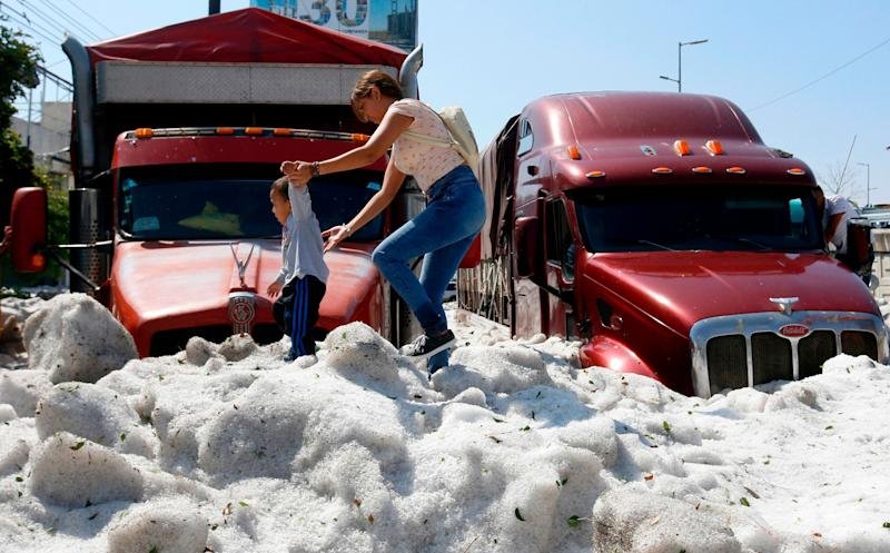 A woman and a child walk on hail in the eastern area of Guadalajara, Jalisco state, Mexico, on June 30, 2019.
