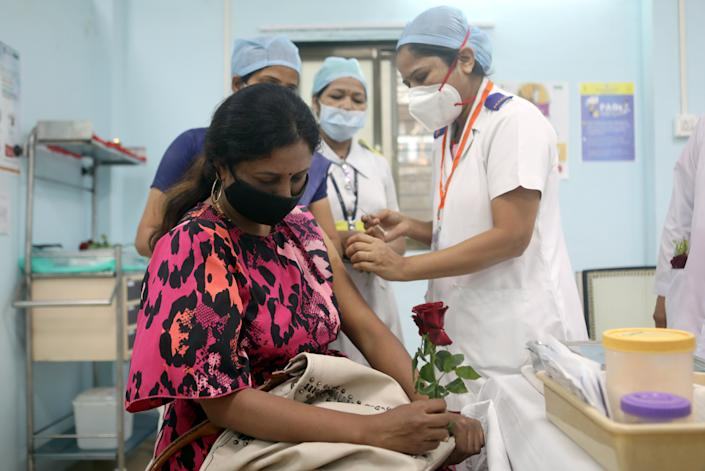 A healthcare worker holding a rose receives an AstraZeneca's COVISHIELD vaccine, during the coronavirus disease (COVID-19) vaccination campaign, at a medical centre in Mumbai, India, January 16, 2021.REUTERS