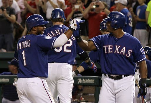 Texas Rangers' Elvis Andrus, left, and Adrian Beltre, right, celebrate after Andrus scored on a two-run home run by Josh Hamilton, rear, in the fifth inning of a baseball game against the Tampa Bay Rays, Friday, April 27, 2012, in Arlington, Texas. The shot came off a pitch from Rays starter James Shields. (AP Photo/Tony Gutierrez)