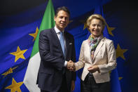 FILE - In this Wednesday, Sept. 11, 2019 file photo, European Commission President Ursula von der Leyen, right, shakes hands with Italian Prime Minister Giuseppe Conte prior to a meeting at the EU Charlemagne building in Brussels. When Giuseppe Conte exited the premier's office, palace employees warmly applauded in him appreciation. But that's hardly likely to be Conte's last hurrah in politics. Just a few hours after the handover-ceremony to transfer power to Mario Draghi, the former European Central Bank chief now tasked with leading Italy in the pandemic, Conte dashed off a thank-you note to citizens that sounded more like an ''arrivederci″ (see you again) then a retreat from the political world he was unexpectedly propelled into in 2018. (AP Photo/Francisco Seco, Pool)