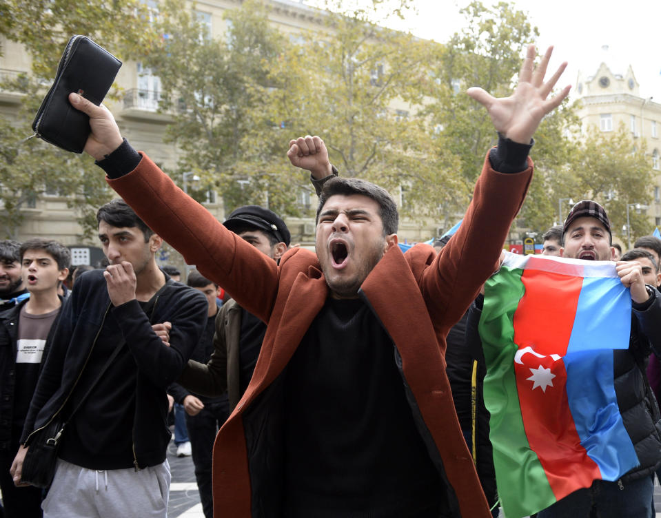 Azerbaijanis celebrate with national flags in Baku, Azerbaijan, Tuesday, Nov. 10, 2020. Armenia and Azerbaijan announced an agreement early Tuesday to halt fighting over the Nagorno-Karabakh region of Azerbaijan under a pact signed with Russia that calls for deployment of nearly 2,000 Russian peacekeepers and territorial concessions. (AP Photo)
