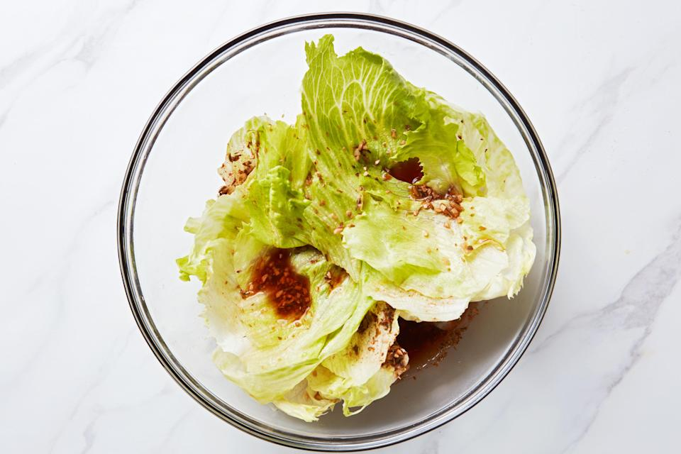 Layering the lettuce and brine ensures the leaves pickle evenly.