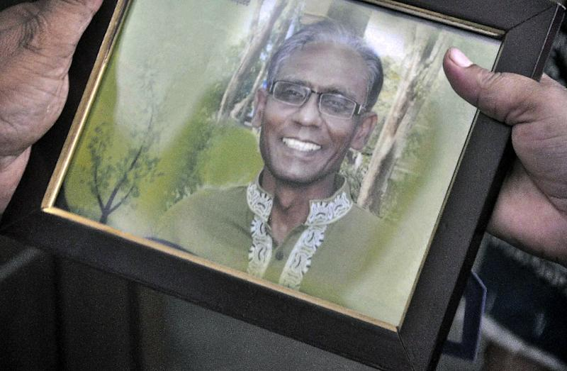 A man holds a portrait of Bangladeshi professor Rezaul Karim Siddique, who was hacked to death by unidentified attackers, in Rajshahi on April 23, 2016 (AFP Photo/MD. Abdullah Iqbal)