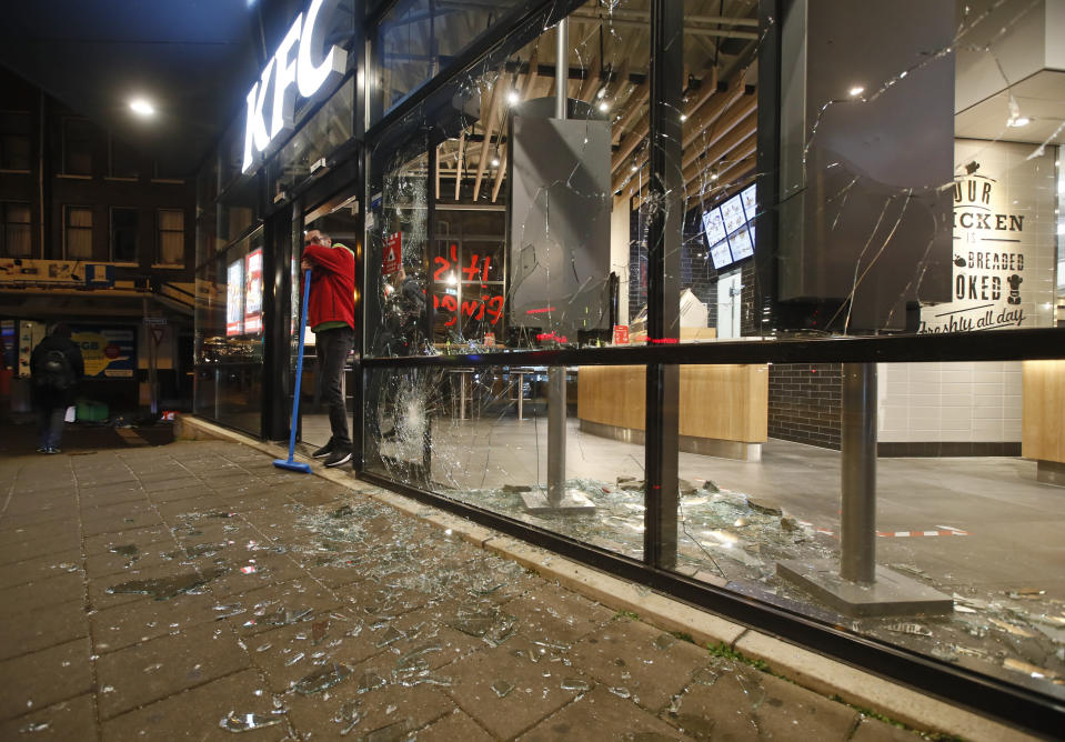 A man rests on his broom as he stands next to shards of glass and smashed windows of a fast-food restaurant that was damaged in protests against a nation-wide curfew in Rotterdam, Netherlands, Monday, Jan. 25, 2021. The Netherlands Saturday entered its toughest phase of anti-coronavirus restrictions to date, imposing a nationwide night-time curfew from 9 p.m. until 4:30 a.m. in a bid to control the COVID-19 infection rate. (AP Photo/Peter Dejong)