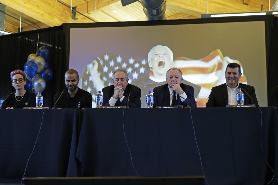 From left to right, Megan Rapinoe, a forward with the National Women's Soccer League's Reign FC and the U.S. Women's National Team, former NBA basketball star Tony Parker, OL Groupe's Gerard Houllier, Jean-Michel Aulas, owner and president of the French soccer team Olympique Lyonnais, and Bill Predmore, former owner of the National Women's Soccer League Reign FC team, watch a video presentation, Thursday, Dec. 19, 2019, during a news conference in Tacoma, Wash. OL Groupe, the parent company of Olympique Lyonnais, is buying Reign FC, of the in a transaction expected to close in January 2020. Reign FC will continue to play its home games at Cheney Stadium, the venue it shares with the Triple-A minor league baseball team the Tacoma Rainiers. (AP Photo/Ted S. Warren)