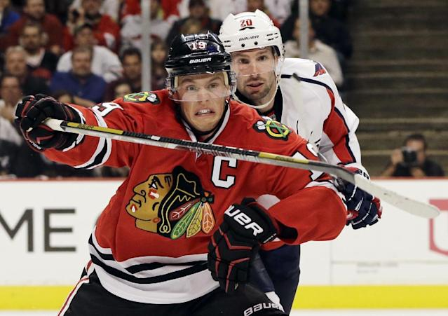 Chicago Blackhawks' Jonathan Toews (19) and Washington Capitals' Troy Brouwer (20) battle as they chase the puck during the second period of an NHL hockey game on Tuesday, Oct. 1, 2013, in Chicago. (AP Photo/Nam Y. Huh)