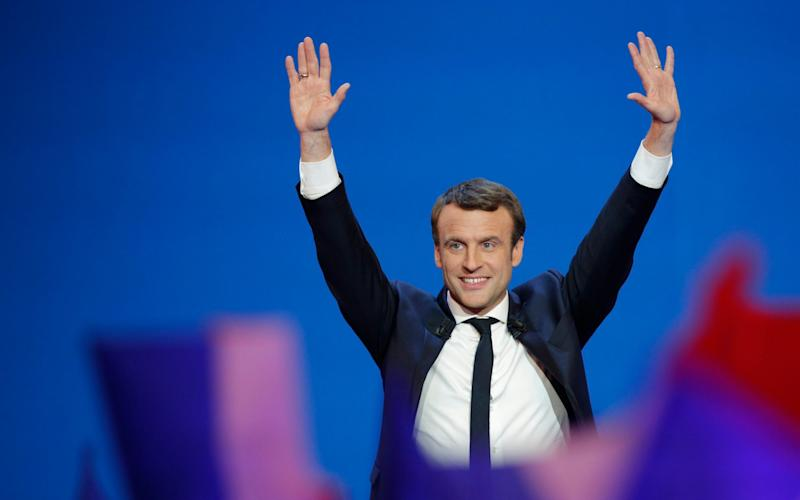 French centrist presidential candidate Emmanuel Macron waves before addressing his supporters at his election day headquarters in Paris - Credit: AP