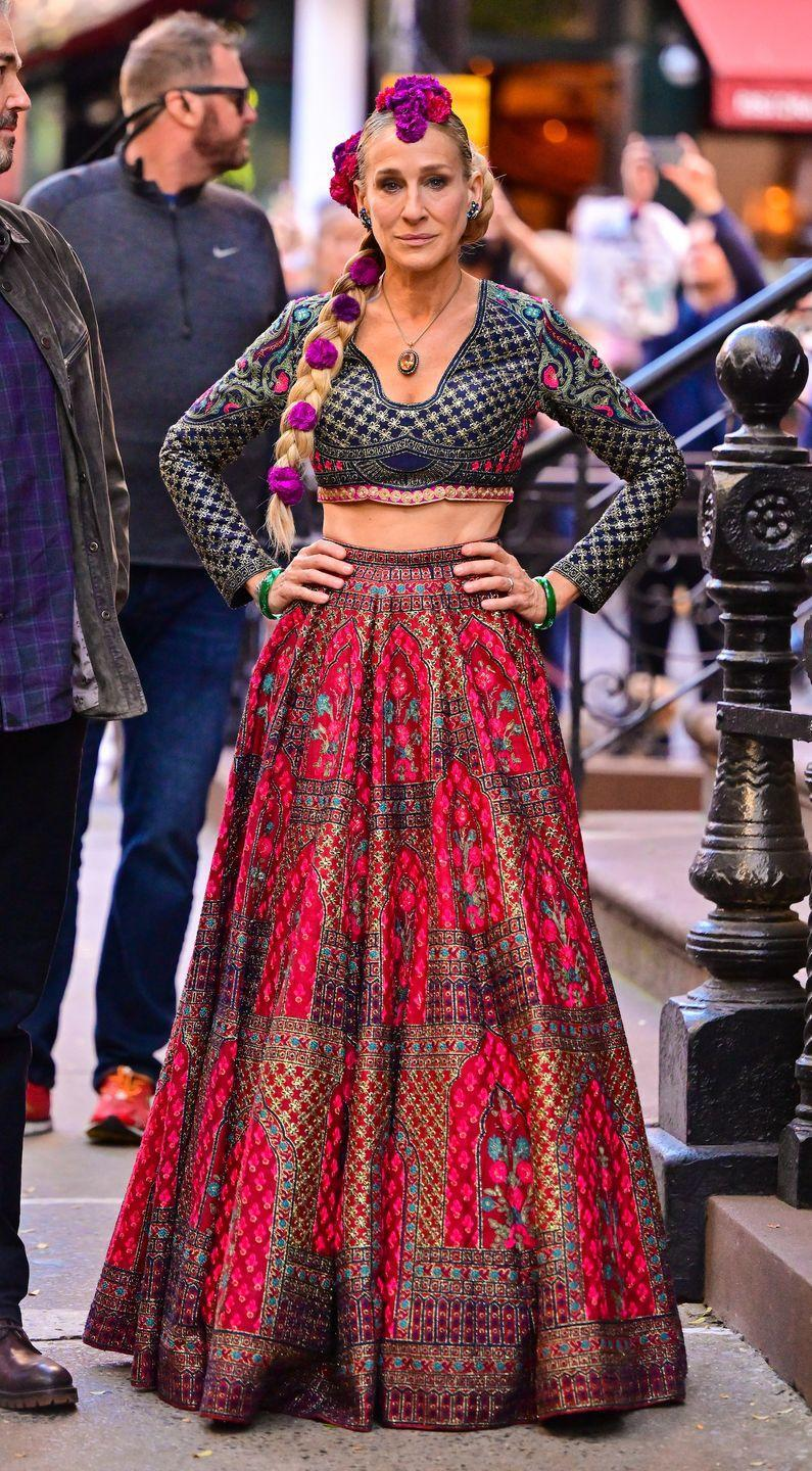 """<p>SJP was photographed wearing a traditional maroon lehenga designed by Indian designers Falguni and Shane Peacock. </p><p>The duo's <a href=""""https://falgunishanepeacock.in/lekha-lehenga-set-mon-amour-jag-niwas"""" rel=""""nofollow noopener"""" target=""""_blank"""" data-ylk=""""slk:website"""" class=""""link rapid-noclick-resp"""">website</a> describes the outfit as having 'multicoloured silk threads embroidery over arch and foliage motifs' and is 'teamed with a full-sleeved navy blue blouse embroidered with gold metal thread-work details, a winged-panel, tassel details and a tulle dupatta'. </p>"""