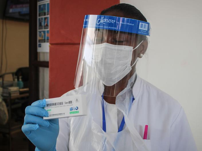 A medical worker wearing a face shield and face mask holds up a small box of vaccines in his blue-gloved hand.