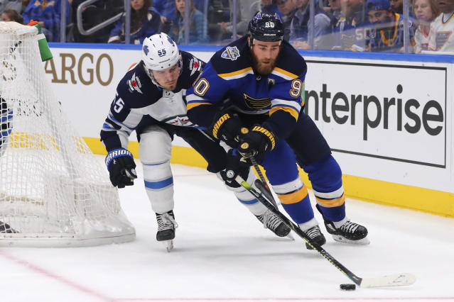 Winnipeg Jets Mark Scheifele (55) pokes the puck away from St. Louis Blues center Ryan O'Reilly (90) during the second period of an NHL hockey game Sunday, Dec. 29, 2019, in St. Louis. (AP Photo/Dilip Vishwanat)