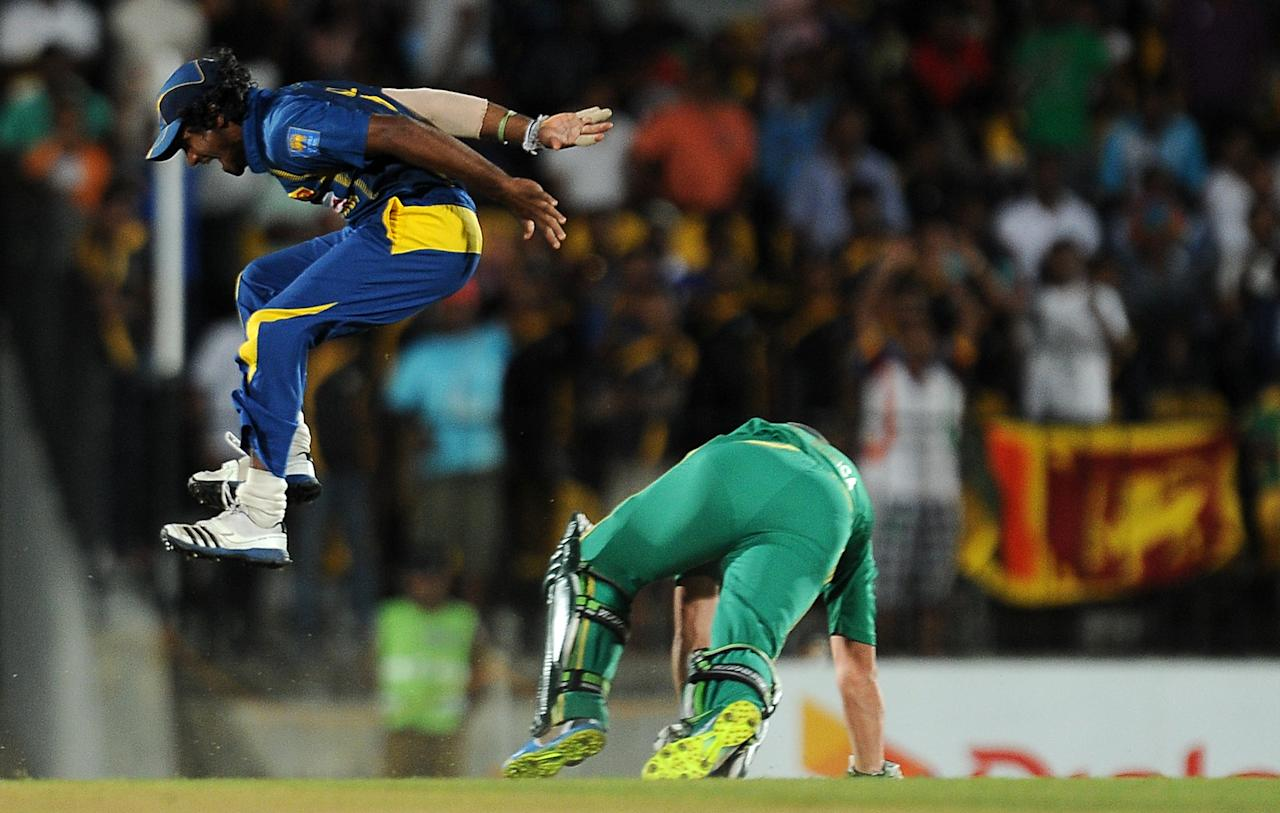Sri Lankan cricketer Kusal Perera (L) leaps into the air after he dismissed South African batsman AB de Villiers during the second Twenty20 cricket match between Sri Lanka and South Africa at the Suriyawewa Mahinda Rajapakse International Cricket Stadium in the southern district of Hambantota on August 4,2013. AFP PHOTO / LAKRUWAN WANNIARACHCHI