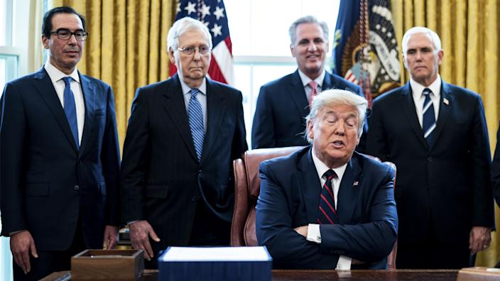 U.S. President Donald Trump speaks before signing the H.R. 748, Coronavirus Aid, Relief, and Economic Security (CARES) Act, in the Oval Office of the White House in Washington, D.C., U.S., on Friday, March 27, 2020. (Erin Schaff/The New York Times/Bloomberg via Getty Images)