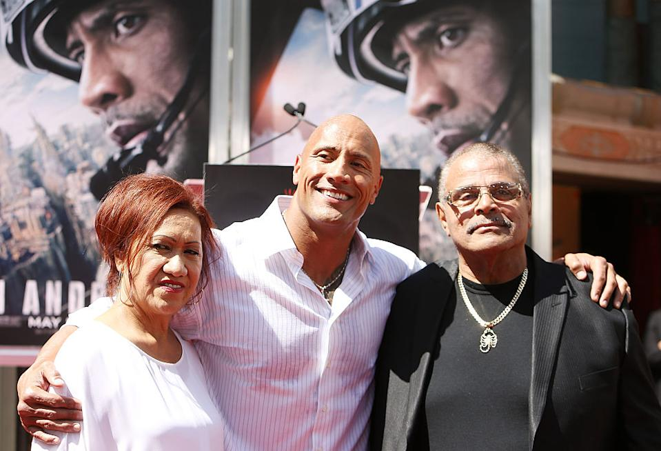 """Dwayne """"The Rock"""" Johnson parents, Ata and Rocky, were by his side at his May 2015 hand and footprint ceremony at TCL Chinese Theatre in Hollywood, Calif. (Photo: Michael Tran/FilmMagic)"""