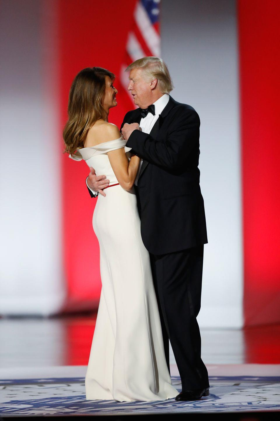 <p>Donald Trump and his wife, Melania Trump, dance at the inaugural ball honoring his appointment as the 45th President of the United States. For the evening's events, the First Lady wore an off-the-shoulder white gown with a red sash, designed by Carolina Herrera's former creative director, Hervé Pierre. </p>