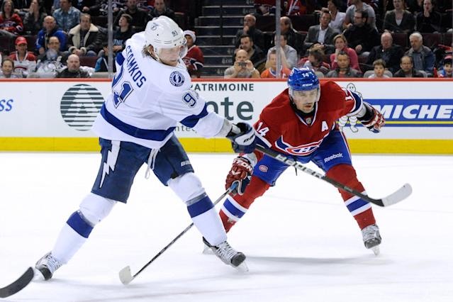 MONTREAL, CANADA - APRIL 4: Steven Stamkos #91 of the Tampa Bay Lightning shoots the puck in front of Tomas Plekanec #14 of the Montreal Canadiens during the NHL game at the Bell Centre on April 4, 2012 in Montreal, Quebec, Canada. The Canadiens defeated the Lightning 5-2. (Photo by Richard Wolowicz/Getty Images)