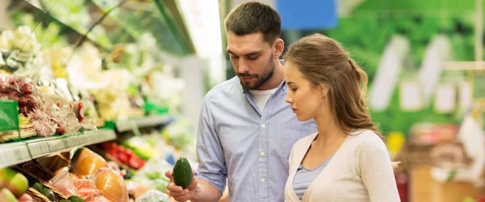 Couple shopping for produce at grocery store.