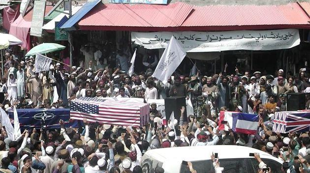 <strong>Crowd carries makeshift coffins draped in NATO's, US and a Union Jack flags during a mock funeral on a street in Khost, Afghanistan.</strong> (Photo: ZHMAN TV via ZHMAN TV via REUTERS)