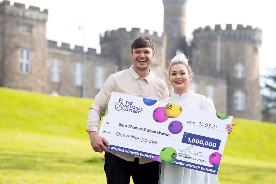 Care home assistant Sara Thomas, 26, and her partner with their winning check.