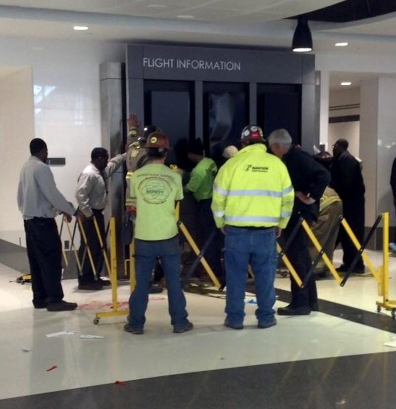 People hold up a message board sign that fell on a family killing a child and injuring the mother and two other children in the terminal at the Birmingham-Shuttlesworth International Airport in Birmingham, Ala., Friday, March 22, 2013.   (AP Photo/ AL.com, Carol Robinson) MAGS OUT