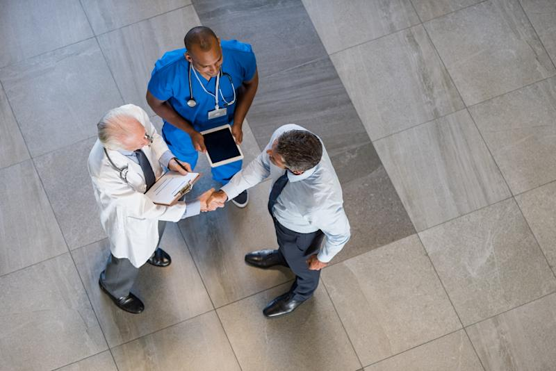 A doctor, a nurse, and a man in a suit stand in a hallway.