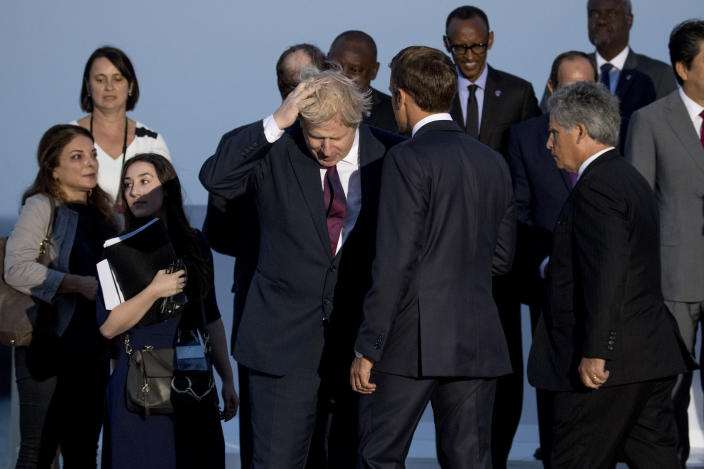 British Prime Minister Boris Johnson, center left, and French President Emmanuel Macron, center right, arrive for the G-7 family photo at the G-7 summit at the Hotel du Palais in Biarritz, France, Sunday, Aug. 25, 2019. (AP Photo/Andrew Harnik)