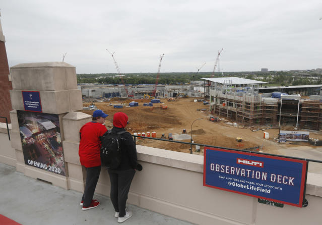 FILe - In this April 7, 2018, file photo, fans look over the construction site of the new Texas Rangers ballpark from Globe Life Field prior to a baseball game against the Toronto Blue Jays in Arlington, Texas. The new ballpark. which is expected to open in 2020, will use specially designed synthetic playing surface rather than grass in their new retractable-roof stadium. (AP Photo/Michael Ainsworth, File)
