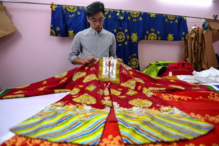 Nguyen Duc Loc, founder of the Y Van Hien company, checking an outfit based on traditional patterns at his workshop in Hanoi
