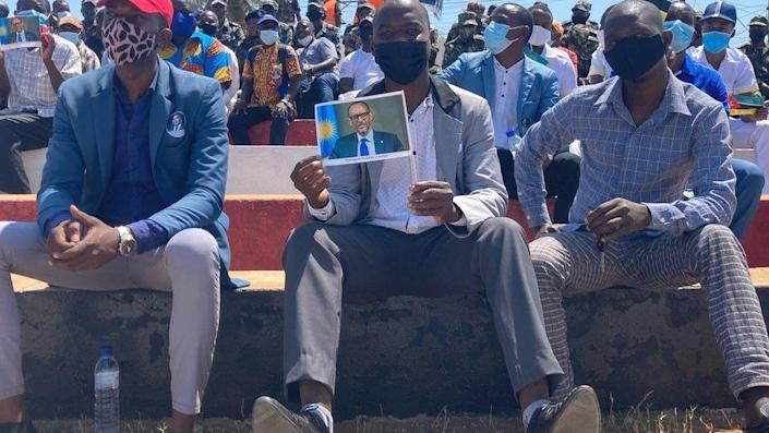 People in a crowd in Pemba hold up pictures of Rwanda's President Paul Kagame at an event to greet him during his two-day visit to Cabo Delgado in September