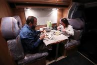 Customers enjoy a dinner sitting inside a motorhome (camping car) parked on the parking of the Belgian restaurant Matthias And Sea despite the lockdown amid the coronavirus disease (COVID-19) pandemic in Tarcienne
