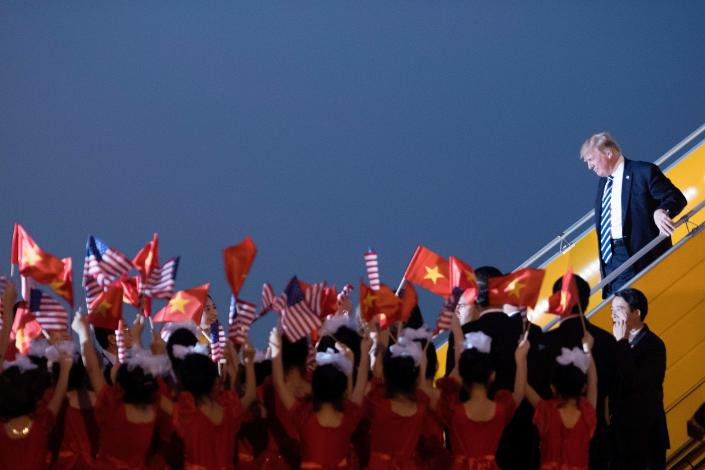 <p>President Donald Trump looks on a young girls wave U.S. and Vietnamese flags as he arrives in Hanoi on Nov. 11, 2017. Trump arrived in the Vietnamese capital after attending the Asia-Pacific Economic Cooperation (APEC) Summit leaders meetings earlier in the day in Danang. (Photo: Jim Watson/AFP/Getty Images) </p>