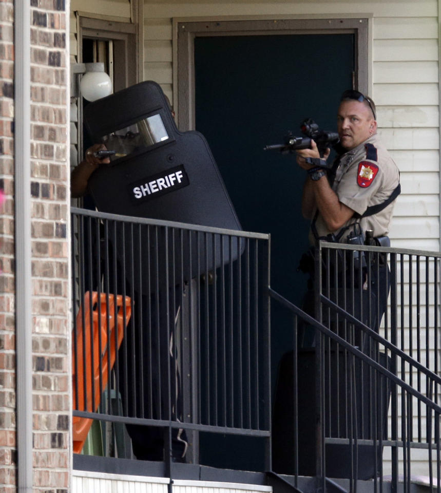 Law enforcement officers wait to enter an apartment near the scene where a mother was killed and her baby kidnapped Tuesday, April 17, 2012, in Spring, Texas. A newborn boy was abducted from his screaming mother after she was repeatedly shot outside a suburban Houston pediatric center on Tuesday, according to investigators searching for the suspected shooter who sped off with the infant in a blood-stained Lexus. (AP Photo/David J. Phillip)