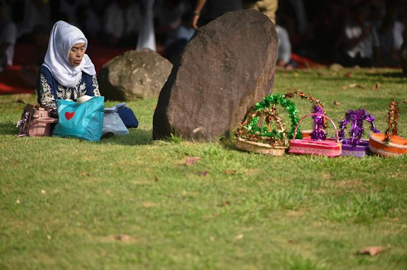A woman prays during a visit to a mass cemetery where thousands of the 2004 tsunami victims are buried (AFP Photo/Chaideer MAHYUDDIN)