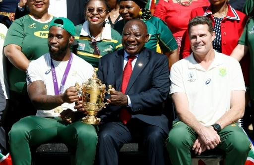 head coach of South Africa, pose for a photograph with South Africa's Springboks rugby captain Siya Kolisi (2ndL) and South African President Cyril Ramaphosa (2ndR), hold the Web Ellis Trophy at the Union Buildings in Pretoria, on November 7, 2019.  The visit by the national team signifies the start of the Rugby World Champion' National Trophy Tour that will see the Cup being paraded in Johannesburg, Durban, East London, Port Elizabeth and Cape Town
