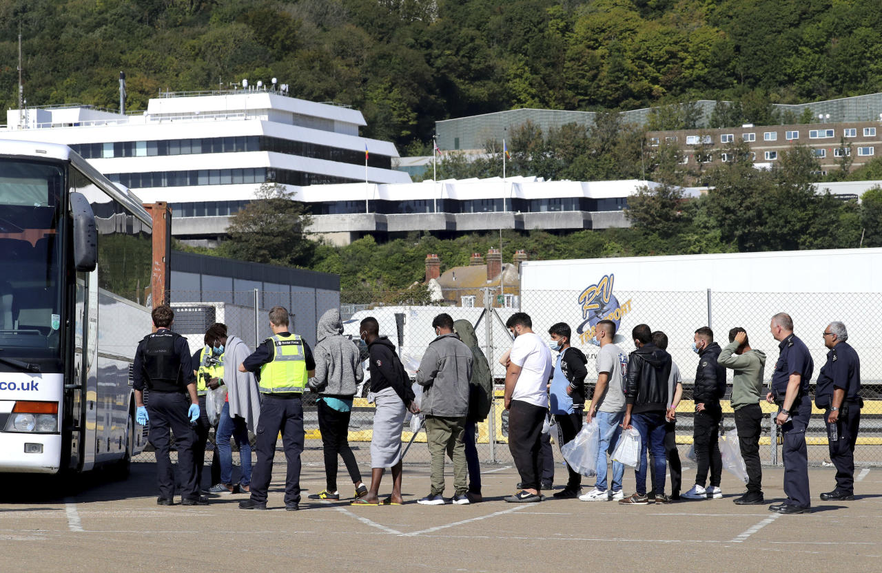 Border Force officers escort a group of men thought to be migrants to a waiting bus, after they were brought into the port city of Dover, England, from small boats, Friday Aug. 7, 2020.  There have been a number of small boat incidents over recent days, with some unseaworthy vessels trying to make the journey from France across The Channel, one of the busiest shipping lanes in the world. (Gareth Fuller/PA via AP)