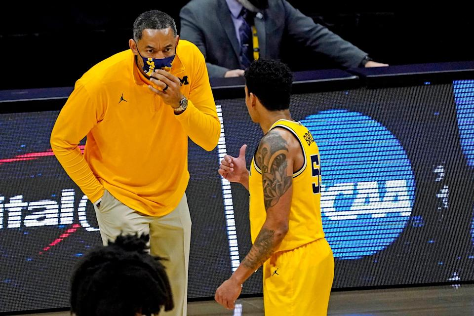 Michigan coach Juwan Howard speaks with guard Eli Brooks during the second half of the Elite Eight game in the NCAA tournament on Tuesday, March 30, 2021, in Indianapolis.