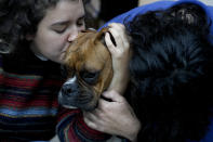 Agustina Ancales and her partner Pablo Vazquez pose for a photo with their dog Sigmoide in Lomas de Zamora, Argentina, Wednesday, Sept. 8, 2021. Ancales' mother got the dog for the couple as a gift after Vazquez was diagnosed with cancer during the COVID-19 lockdown to try to cheer them up. (AP Photo/Natacha Pisarenko)
