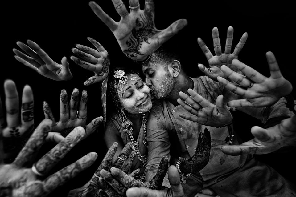 <p>A newlywed couple kiss before a sea of henna-ed hands. <em>[Photo: <span>SHUTTERINK PHOTOGRAPHY / JUNEBUG WEDDINGS / CATERS]</span></em> </p>