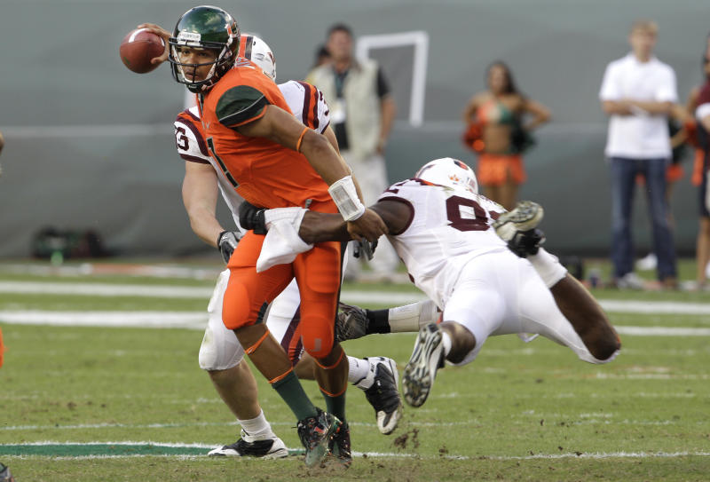 University of Miami quarterback Stephen Morris, left, is pressured by Virginia Tech defensive end Steven Friday, right, in the second quarter during an NCAA college football game in Miami, Saturday, Nov. 20, 2010. (AP Photo/Lynne Sladky)