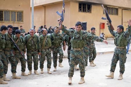 FILE PHOTO: Fighters from a new border security force under the command of Syrian Democratic Forces (SDF) dance during a graduation ceremony in Hasaka