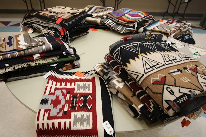 Part of a collection of 425 Navajo weavings from the estate of Bob Culpepper is arranged on a table at the Farmington Museum at Gateway Park on Aug. 6.