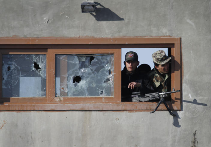 Afghan soldiers watch the protestors from the window of a guard tower during an anti-U.S. demonstration in Kabul, Afghanistan, Friday, Feb. 24, 2012. Thousands of Afghans staged new demonstrations Friday over the burning of Qurans at a U.S. military base in Afghanistan. (AP Photo/Ahmad Jamshid)