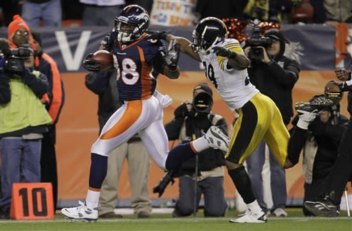 CORRECTS SCORE - Denver Broncos wide receiver Demaryius Thomas (88) breaks away from Pittsburgh Steelers defensive back Ryan Mundy (29) for the winning touchdown in overtime of an NFL wild card playoff football game Sunday, Jan. 8, 2012, in Denver. The Broncos won 29-23. (AP Photo/Joe Mahoney)