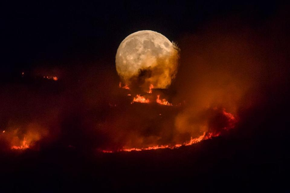 The full moon rises behind burning moorland as a large wildfire sweeps across the moors between Dovestones and Buckton Vale in Stalybridge, Greater Manchester (Picture: Getty)