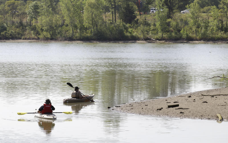 Law enforcement authorities in kayaks search Meyers Lake where Lyric Cook-Morrissey, 10, and Elizabeth Collins, 8, disappeared last Friday, Tuesday, July 17, 2012, in Evansdale, Iowa. The girls' bikes were found Friday afternoon near a bike trail at the edge of the lake. (AP Photo/Charlie Neibergall)